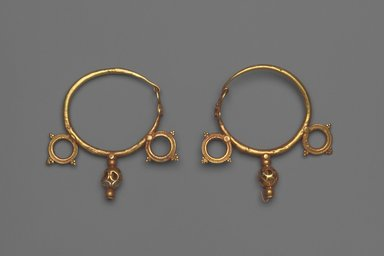 Earrings with Wheel and Pendant Ornaments, 6th century C.E. Gold, 1 3/4 x 1/4 in. (4.4 x 0.6 cm). Brooklyn Museum, Ella C. Woodward Memorial Fund, 05.441a-b. Creative Commons-BY