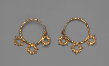 Pair of Earrings with Three Wheel Ornaments, 6th century C.E. Gold, 3/8 x 1 15/16 in. (0.9 x 5 cm). Brooklyn Museum, Ella C. Woodward Memorial Fund, 05.442a-b. Creative Commons-BY