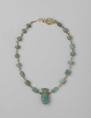Necklace, 1st century C.E. Gold, beryl, silver, Necklace: 13 9/16 in. (34.4 cm) long; Bes figure: 1 x 7.16 in. (2.6 x 1.1 cm). Brooklyn Museum, Gift of Evangeline Wilbour Blashfield, Theodora Wilbour, and Victor Wilbour honoring the wishes of their mother, Charlotte Beebe Wilbour, as a memorial to their father, Charles Edwin Wilbour, 16.149. Creative Commons-BY