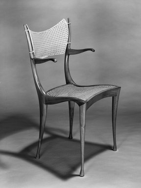 "Dan Johnson Studio, a Division of Arch Industries. ""Gazelle"" Armchair, designed 1956. Walnut, cane, brass, 37 11/16 x 21 x 23in. (95.7 x 53.3 x 58.4cm). Brooklyn Museum, H. Randolph Lever Fund, 1989.113. Creative Commons-BY"