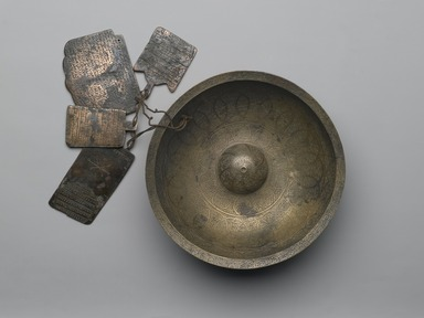 Chihil Kilid (Forty Keys) Divination Bowl with Inscriptions, Zodiac Signs, and Four Plaquettes, 1679. Copper alloy (brass), engraved with repoussé center and inlaid with black composites, 3in. (7.6cm). Brooklyn Museum, Gift of Mrs. Charles K. Wilkinson in memory of her husband, 1989.149.11. Creative Commons-BY