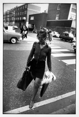Garry Winogrand (American, 1928-1984). Untitled (Woman with Purse and Portfolio Crossing the Street), from Women are Beautiful Series. Gelatin silver photograph, sheet: 14 x 11 in. (35.5 x 27.9 cm). Brooklyn Museum, Gift of Mitchell F. Deutsch, 1995.206.13. © The Estate of Garry Winogrand, courtesy Fraenkel Gallery, San Francisco