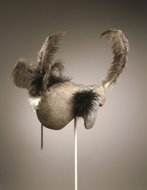 Dongiro. Mudpack Coiffure, 20th century. Organic material, pigment, human hair, plastic beads, ostrich feathers, copper alloy, aluminum, 13 3/4 x 12 1/2 x 15 in. (35.0 x 31.8 x 38.2 cm). Brooklyn Museum, John W. James Fund, 1996.112.1. Creative Commons-BY
