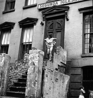Vivian Cherry (American, born 1920). Spanish Harlem (Young Girl on Stairs Holding Her Skirt Up), 1947. Gelatin silver photograph (vintage), 10 15/16 x 10 in. (32.9 x 25.4 cm). Brooklyn Museum, Gift of Steven Schmidt, 1996.241.42. © Vivian Cherry