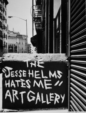 "Arthur Mones (American, 1919-1998). New York, Soho (The ""Jesse Helms Hates Me"" ""Art Gallery""), 1990. Gelatin silver photograph on fiber based paper, sheet: 14 x 10 3/4 in. (35.6 x 27.2 cm). Brooklyn Museum, Gift of the artist, 1997.162.2. © Estate of Arthur Mones"