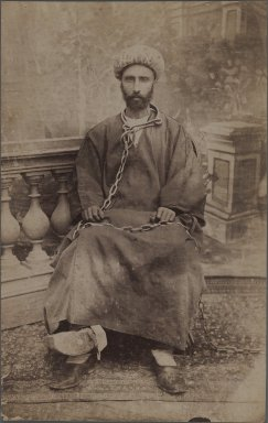 A Political Prisoner in Chains, late 19th-early 20th century. Albumen silver photograph, 8 1/4 x 5 1/4 in.  (21 x 13.3 cm). Brooklyn Museum, Purchase gift of Leona Soudavar in memory of Ahmad Soudavar, 1997.3.112
