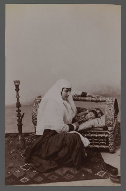 Woman Rocking her Child's Cradle,  One of 274 Vintage Photographs, late 19th-early 20th century. Albumen silver photograph, 8 3/16 x 5 1/4 in.  (20.8 x 13.3 cm). Brooklyn Museum, Purchase gift of Leona Soudavar in memory of Ahmad Soudavar, 1997.3.15