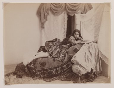 Possibly Antoin Sevruguin. Studio Shot of a Reclining Lady Reading a Book, Late 19th century. Albumen silver photograph, 6 3/16 x 8 1/8 in.  (15.7 x 20.6 cm). Brooklyn Museum, Purchase gift of Leona Soudavar in memory of Ahmad Soudavar, 1997.3.6