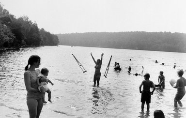 Joel Meyerowitz (American, born 1938). Lake in Catskill Mountains (Woman Throws Crutches), 1971. Gelatin silver photograph, Sheet: 11 x 14 in. (27.9 x 35.6 cm). Brooklyn Museum, Gift of Julian and Elaine Hyman, 2000.132.2. © Joel Meyerowitz