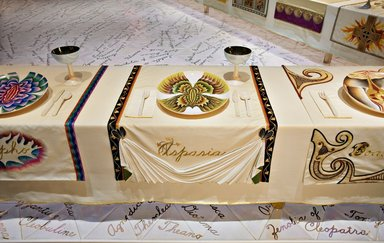 """Judy Chicago (American, born 1939). Aspasia Place Setting, 1974-1979. Runner: Cotton/linen base fabric, woven interface support material (horsehair, wool, and linen), cotton twill tape, silk, stiffened cotton/linen fabric, """"polished cotton"""" fabric, silk thread, metallic cord, cotton, thread Plate: Porcelain with overglaze enamel (China paint), Runner: 52 x 30 in. (132.1 x 76.2 cm). Brooklyn Museum, Gift of The Elizabeth A. Sackler Foundation, 2002.10-PS-11. © Judy Chicago"""