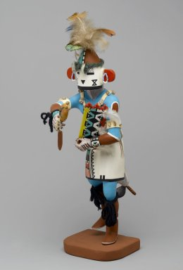 Henry Shelton (born 1929). Kachina Doll, 1960-1970. Cottonwood root, acrylic pigment, yarn, feathers, shell, hide, cotton, beads, 16 1/2 x 4 x 8 in. (41.9 x 10.2 x 20.3 cm). Brooklyn Museum, Gift of Edith and Hershel Samuels, 2010.6.9. Creative Commons-BY