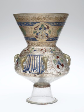 Mosque Lamp, 13th-14th century. Colorless glass; blue, green, red, and white enamels; and gold;  free blown, applied, enameled, and gilded; tooled on the pontil, includes base, now detached: 12 x 8 in. (30.5 x 20.3 cm). Brooklyn Museum, Bequest of William H. Herriman, 21.484. Creative Commons-BY