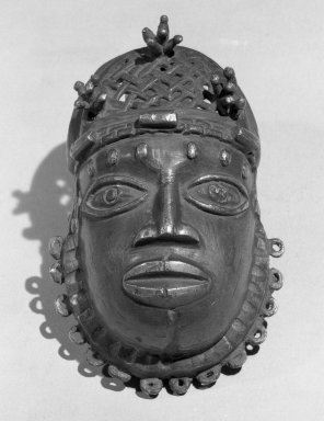 Edo. Pendant Mask (Uhunmwun-ekue), 19th century. Copper alloy, 4 x 3 in.  (10.2 x 7.6 cm). Brooklyn Museum, Museum Expedition 1923, Purchased with funds given by Frederic B. Pratt and Frank L. Babbott, 23.280. Creative Commons-BY