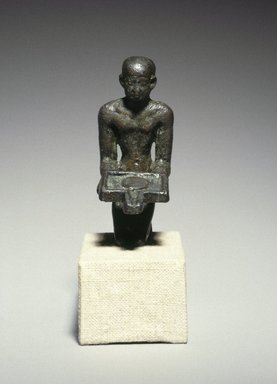 Egyptian Priest Kneeling with Offering Table, ca. 1539 B.C.E. or later. Bronze, 2 1/2 x 13/16 x 1 7/16 in. (6.4 x 2.1 x 3.7 cm). Brooklyn Museum, Charles Edwin Wilbour Fund, 37.362E. Creative Commons-BY