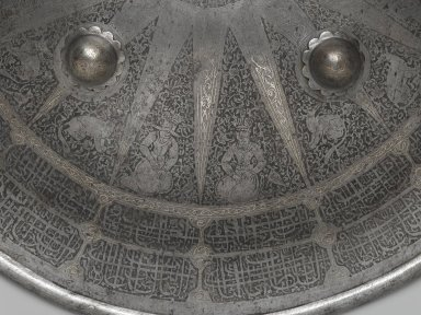 Shield with Arabic Inscription and Signs of the Zodiac, 19th century. Iron alloy (steel), etched and overlaid with silver and gold; fabric lining, Diam. 18 5/8 in. (47.3 cm). Brooklyn Museum, Gift of Percy C. Madeira, Jr., 42.245.2. Creative Commons-BY