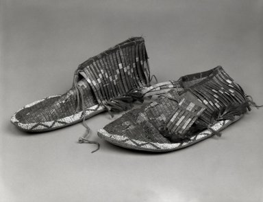 Klikitat (Native American). Pair of Embroidered Moccasins, ca 1870s. Buffalo calfskin, porcupine quills, beads, horsehair, woodpecker feathers, tin, 3 15/16 x 11 7/16 x 3 15/16 in. (10 x 29.1 x 10 cm). Brooklyn Museum, Gift of Edna Ebling, 44.203a-b. Creative Commons-BY