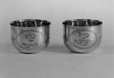 Hester Bateman (English, active in London, 1774-1789). Jewish Ceremonial Wine Cup, One of Pair, 1785-1786 with late 19th-century inscriptions. Silver, 1 3/4 x 2 7/16 x 2 7/16 in. (4.4 x 6.2 x 6.2 cm). Brooklyn Museum, Ella C. Woodward Memorial Fund, 51.110.1. Creative Commons-BY