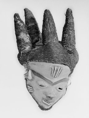 Pende (Western). Mask (Mbuya) of Chief (Phumbu), late 19th-early 20th century. Wood, pigment, raffia, fiber, 17 5/16 x 11 in.  (44.0 x 27.9 cm). Brooklyn Museum, Gift of Arturo and Paul Peralta-Ramos, 56.6.4. Creative Commons-BY