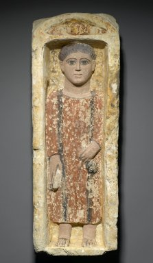 Funerary Stela with Boy Standing in a Niche, 4th-5th century C.E. Limestone, ancient and modern paint in ochre, dark terracotta, brown, black and flesh-tone, 27 9/16 x 9 5/8 x 6 1/2 in. (70 x 24.5 x 16.5 cm). Brooklyn Museum, Charles Edwin Wilbour Fund, 58.129. Creative Commons-BY