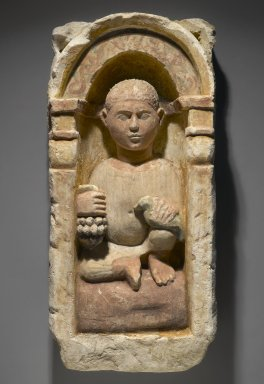 Funerary Stela with Boy Seated in a Niche, 4th-5th century C.E. Limestone, ancient and modern paint, 26 9/16 x 12 5/8 x 6 3/16 in. (67.5 x 32 x 15.7 cm). Brooklyn Museum, Charles Edwin Wilbour Fund, 71.39.2. Creative Commons-BY