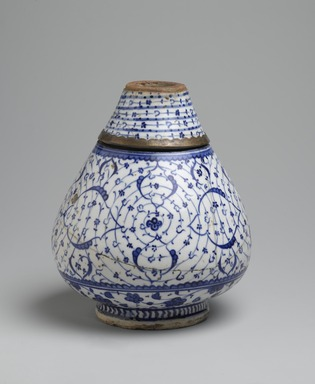 "Flask in Two Sections with ""Golden Horn"" or Tugrakes Motif, first half of 16th century. Ceramic; fritware, painted in cobalt blue under a transparent glaze; 19th-century brass mount, Height of bottom: 6 in. (15.2 cm). Brooklyn Museum, Special Middle Eastern Art Fund, 73.66.3a-c. Creative Commons-BY"