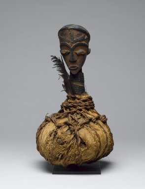 Tsogho. Reliquary Guardian Figure (Boumba Bwiti), late 19th or early 20th century. Wood, raffia, metal, bark cloth, glass, feathers, 12 x 7 1/2 in. (30.5 x 18.4 cm). Brooklyn Museum, Gift of Mr. and Mrs. John A. Friede, 74.121.7. Creative Commons-BY