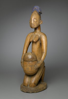 Possibly Maku, master carver of Erin (died 1915). Kneeling Female Figure (Arugba), early  20th century. Wood, pigment, 22 x 7 x 8 in. (55.9 x 17.8 x 20.3 cm). Brooklyn Museum, Gift of Dr. and Mrs. Robert A. Mandelbaum, 82.103a-b. Creative Commons-BY