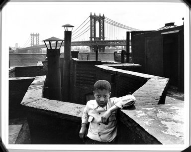 "Walter Rosenblum (American, 1919-2006). ""Boy on Roof"" Monroe Street, New York, 1950. Gelatin silver photograph on white wove paper, sheet: 11 x 14 in.  (27.9 x 35.6 cm); image: 10 3/4 x 13 1/4 in. (27.3 x 33.7 cm). Brooklyn Museum, Gift of Lisa Rosenblum, 84.236.9. © Rosenblum Archive"