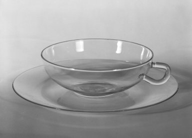 Wilhelm Wagenfeld (1900-1990). Cup and Saucer, 1930-1934. Clear heat-resistant glass, 1 3/8 x 5 1/8 x 3 7/8 in. (3.5 x 13 x 9.8 cm). Brooklyn Museum, Gift of Barry Friedman, 84.64.9a-b. Creative Commons-BY