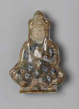Tile in the Shape of a Seated Figure, early 13th century. Ceramic; fritware, molded and painted in luster and cobalt blue on an opaque white glaze, 5 1/2 x 4in. (14 x 10.2cm). Brooklyn Museum, Gift of the Ernest Erickson Foundation, Inc., 86.227.69. Creative Commons-BY