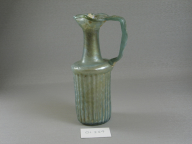 Roman. Molded Jug, 1st century C.E. Glass, 6 11/16 x 2 11/16 x 3 3/4 in. (17 x 6.9 x 9.5 cm). Brooklyn Museum, Gift of Robert B. Woodward, 01.259. Creative Commons-BY