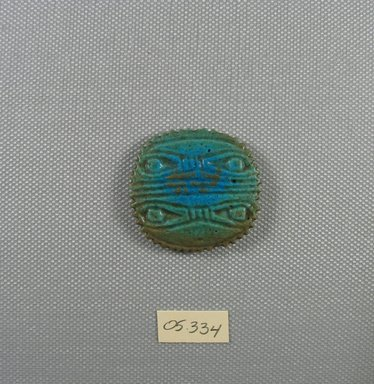 Blue-green Glazed Faience Oval Amulet with Two Double Divine Eyes on Each Side. Faience, glazed, 1 5/16 x 1/4 x 1 7/16 in. (3.4 x 0.6 x 3.7 cm). Brooklyn Museum, Charles Edwin Wilbour Fund, 05.334. Creative Commons-BY