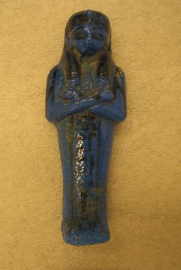 Ushabti, ca. 1075-945 B.C.E. Faience, glazed, height: 4 5/16 in. (11 cm); width at elbows: 1 5/8 in. (4.1 cm). Brooklyn Museum, Gift of Evangeline Wilbour Blashfield, Theodora Wilbour, and Victor Wilbour honoring the wishes of their mother, Charlotte Beebe Wilbour, as a memorial to their father, Charles Edwin Wilbour, 16.177. Creative Commons-BY