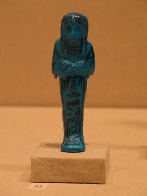 Funerary Figurine of King Pinudjem I, ca. 1025-1007 B.C.E. Faience, 4 1/4 x Width at elbows  1 5/16 in. (10.8 x 3.4 cm). Brooklyn Museum, Gift of Evangeline Wilbour Blashfield, Theodora Wilbour, and Victor Wilbour honoring the wishes of their mother, Charlotte Beebe Wilbour, as a memorial to their father, Charles Edwin Wilbour, 16.189. Creative Commons-BY