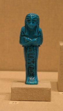 Shabty of Pinudjem I, ca. 1025-1007 B.C.E. Faience, 4 1/8 x W. at elbows 1 7/16 in. (10.4 x 3.7 cm). Brooklyn Museum, Gift of Evangeline Wilbour Blashfield, Theodora Wilbour, and Victor Wilbour honoring the wishes of their mother, Charlotte Beebe Wilbour, as a memorial to their father, Charles Edwin Wilbour, 16.190. Creative Commons-BY