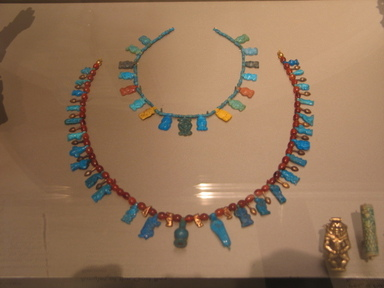 Necklace with Bes and Taweret Pendants, ca. 1539-1292 B.C.E. Gold, faience, carnelian, Length: 6 in. (15.2 cm). Brooklyn Museum, Gift of Evangeline Wilbour Blashfield, Theodora Wilbour, and Victor Wilbour honoring the wishes of their mother, Charlotte Beebe Wilbour, as a memorial to their father Charles Edwin Wilbour, 16.580.201. Creative Commons-BY