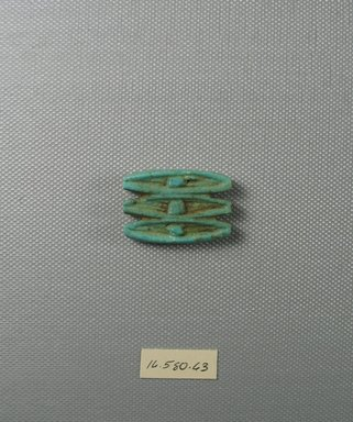 Triple Divine-eye as Amulet. Faience, 1 5/16 x 1/4 x 1 1/4 in. (3.3 x 0.6 x 3.1 cm). Brooklyn Museum, Gift of Evangeline Wilbour Blashfield, Theodora Wilbour, and Victor Wilbour honoring the wishes of their mother, Charlotte Beebe Wilbour, as a memorial to their father Charles Edwin Wilbour, 16.580.63. Creative Commons-BY