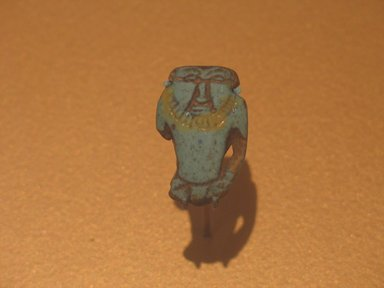 Amulet of Bes-image, ca. 1836-1700 B.C.E. Faience, 1 1/4 x 13/16 x 3/8 in. (3.2 x 2.1 x 1 cm). Brooklyn Museum, Gift of Ariane, Nike, and Samara Mele, 1990.13. Creative Commons-BY