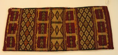 Berber, Zemmour Tribe. Bolster Cover, mid 20th century. Wool, flat weave, cotton brocade, sequins, 17 1/2 x 14 1/2 x 33 7/8 in. (44.5 x 36.8 x 86 cm). Brooklyn Museum, Gift of Dr. Virgil H. Bird, 1994.189.1. Creative Commons-BY