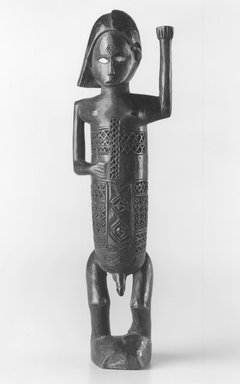 Kongo (Beembe subgroup). Figure of a Standing Male with Left Arm Raised (Mukuya), 19th or 20th century. Wood, ceramic, 8 1/2 x 2 1/2 x 1 3/4 in. (21.6 x 6.4 x 4.5 cm). Brooklyn Museum, Gift of Drs. Noble and Jean Endicott, 1995.173.3. Creative Commons-BY