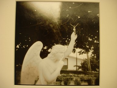 Jonathan Bailey (American, born 1954). Isla Mujeres (Quintanar Roo), Mexico, (Angel Holding Christ), Cemetery: Isla Mujeres, 1990. Split-toned gelatin silver photographs, image: 5 1/2 x 5 1/2 in. (14 x 14 cm). Brooklyn Museum, Gift of the artist, 2000.65.1. © Jonathan Bailey