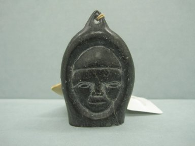 Samwillie Amidlak (1902-1984). Janus-faced Amulet Head, 1950-1980. Black stone, 2 3/4 x 1 7/8 x 3/4 in. (7 x 4.8 x 1.9 cm). Brooklyn Museum, Hilda and Al Schein Collection, 2004.79.19. Creative Commons-BY