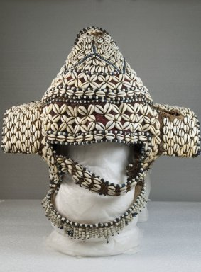Kuba. Headdress, late 19th or early 20th century. Cowrie shell, fiber, wood, 13 3/4 x 13 3/8 in.  (34.9 x 34.0 cm). Brooklyn Museum, Museum Expedition 1922, Robert B. Woodward Memorial Fund, 22.1443. Creative Commons-BY