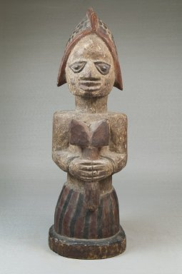 Yoruba. Figure of a Devotee of Shango Holding an Oshe Shango, late 19th or early 20th century. Wood, pigment, 15 x 4 15/16 x 5 3/4 in. (38.1 x 12.5 x 14.6 cm). Brooklyn Museum, Museum Expedition 1922, Robert B. Woodward Memorial Fund, 22.1518. Creative Commons-BY