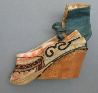 Tiny Shoe for Woman's Bound Foot, 19th century. Wood, plain linen, fancy silk, satin silk, 3 9/16 x 3 9/16 in. (9 x 9 cm). Brooklyn Museum, Brooklyn Museum Collection, 34.1379. Creative Commons-BY