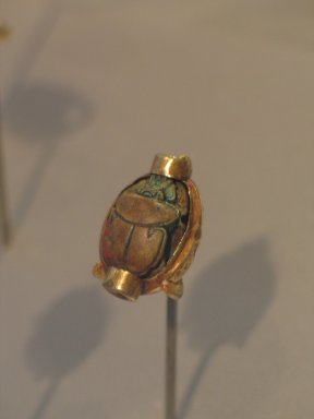 Scarab of Hatshepsut in Mount, ca. 1478-1458 B.C.E. Gold, and steatite, glazed, 9/16 x 7/8 in. (1.4 x 2.2 cm). Brooklyn Museum, Gift of Theodora Wilbour from the collection of her father, Charles Edwin Wilbour, 35.1118. Creative Commons-BY