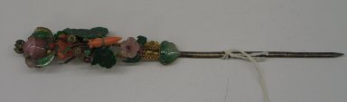 Hair Pin, Early 20th century. Gilt, jade, coral, garnet, pink tourmaline, feather, 11 7/16 x 1 in. (29.1 x 2.5 cm). Brooklyn Museum, Frank L. Babbott Fund, 37.371.250. Creative Commons-BY