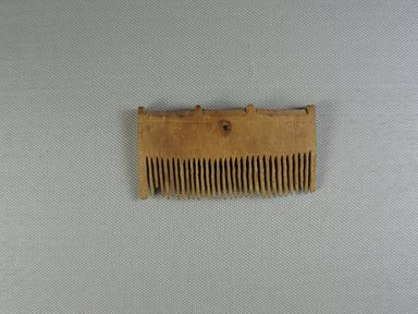 Comb Surmounted by Four Knobs. Wood, 1 11/16 x 3/8 x 3 1/4 in. (4.3 x 0.9 x 8.2 cm). Brooklyn Museum, Charles Edwin Wilbour Fund, 37.653E. Creative Commons-BY