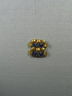 Clasp Fragment. Gold, carnelian, lapis lazuli, 9/16 x 5/8 x 1/16 in. (1.4 x 1.6 x 0.2 cm). Brooklyn Museum, Charles Edwin Wilbour Fund, 37.703E. Creative Commons-BY