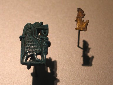 Amulet in the Form of a Seated Mummified King, ca. 1539-1075 B.C.E. Gold, 3/8 x 7/8 in. (0.9 x 2.3 cm) . Brooklyn Museum, Gift of Evangeline Wilbour Blashfield, Theodora Wilbour, and Victor Wilbour honoring the wishes of their mother, Charlotte Beebe Wilbour, as a memorial to their father, Charles Edwin Wilbour, 16.323. Creative Commons-BY